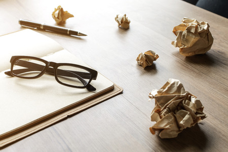 notebook: Crumpled paper balls with eye glasses and notebook on wood desk with soft light Stock Photo