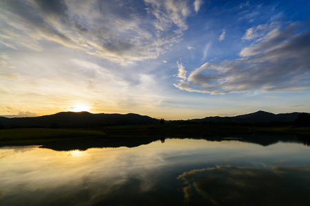 silhoutted: Silhoutted mountain at sunset with peaceful lake reflection and beautiful sky