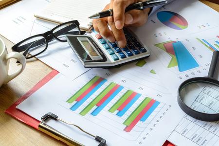 contabilidad financiera cuentas: negocios que trabajan en la oficina tur�stica de negocios calcular la contabilidad financiera, el an�lisis gr�fico Foto de archivo