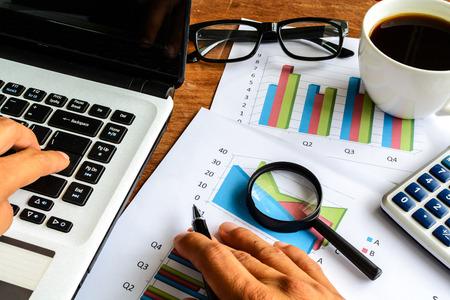 hoja de calculo: Computadora port�til en la oficina tur�stica y el gr�fico de an�lisis de hojas de c�lculo, las finanzas de negocios