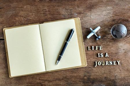 """путешествие: Дневник на деревянном фоне со словом """"Жизнь это путешествие"""" Фото со стока"""