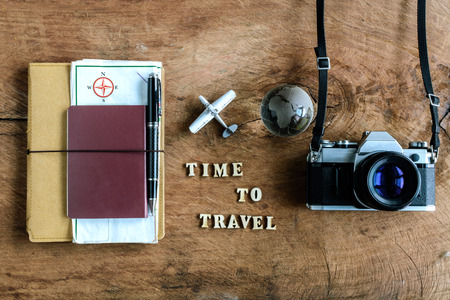camera: Notebook with map, passport and camera on wooden background with word Time to travel Stock Photo