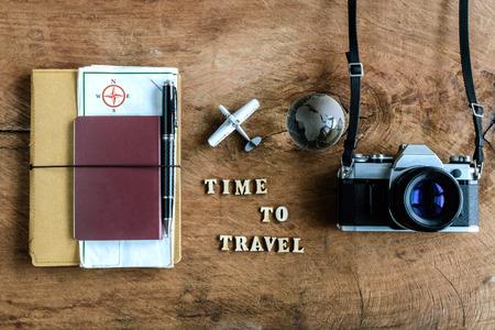 """pasaporte: Portátil con mapa, pasaporte y cámara en el fondo de madera con la palabra """"Tiempo de viajar"""""""