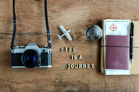 camera: Notebook with map, passport and camera on wooden background with word Life is a journey
