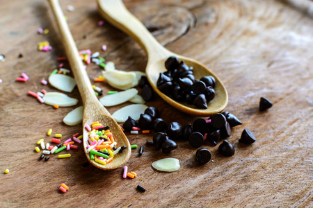 chocolate chips: Chocolate chips on wooden spoon and ingredients for cooking dessert