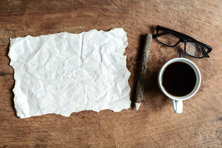 crinkled: wrinkled paper with coffee and wooden pencil on old wooden background