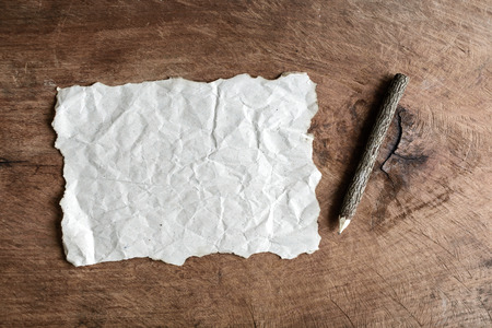 crinkled: wrinkled paper and wooden pencil on old wooden background