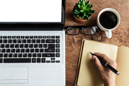 filiżanka kawy: Laptop i kubek kawy z strony pracy na starym drewnianym stole Archiwalne tonowe