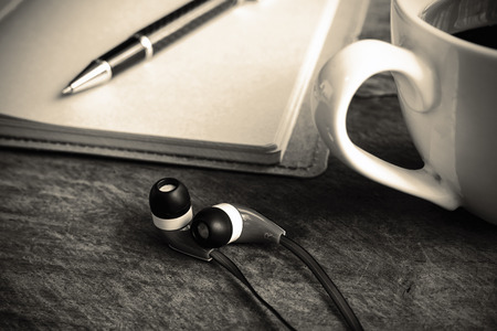 earpiece: close up of earphone with coffee and notebook on old wooden table, sepia tone