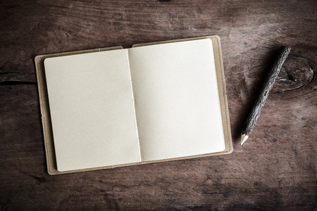 Open blank notebook on wooden table, Vintage tone Standard-Bild