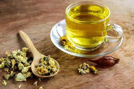 nature cure: Chinese Chrysanthemum Tea on old wooden table Stock Photo