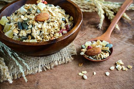 Avena y trigo integral granos escamas en un tazón de madera en la mesa de madera