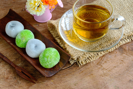 japanese people: Daifuku green tea and sesame filling with cup of tea on wooden table Stock Photo