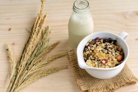 cosecha de trigo: Botella de leche fresca con avena y trigo integral granos escamas en mesa de madera Foto de archivo