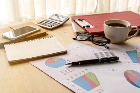 デスク オフィス ビジネス財務会計を柔らかな光、グラフ分析、ビジネスの概念と計算します。