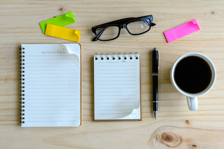 pen and paper: Cup of coffee with blank notebook on wooden desk Stock Photo