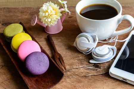 taza cafe: Macarrones coloridos y una taza de café con teléfono celular en la mesa de madera Foto de archivo