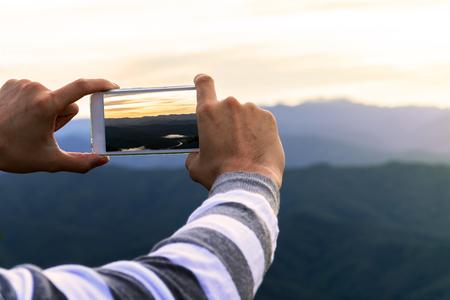 Man using smart phone take a photo mountain view Standard-Bild