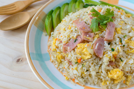 Fried rice with bacon and egg on wooden table