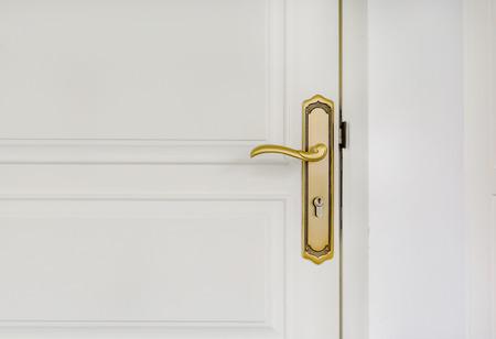 portones de madera: Close up del cl�sico manija de la puerta de oro en puerta blanca