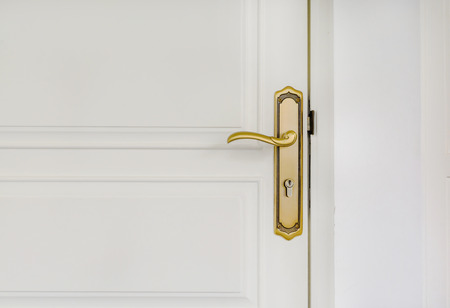 Close up of classic golden door handle on white door