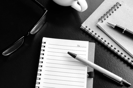 paper and pen: Cup of coffee with notebook on desk office, workplace, Monochrome tone Stock Photo