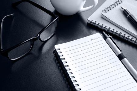 papel de notas: Cup of coffee with notebook on desk office, workplace, Monochrome tone Foto de archivo