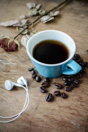 earphone: close up of earphone with coffee on old wooden table Stock Photo
