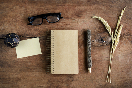 old desk: Blank note book with eye glasses and pencil on old wooden desk