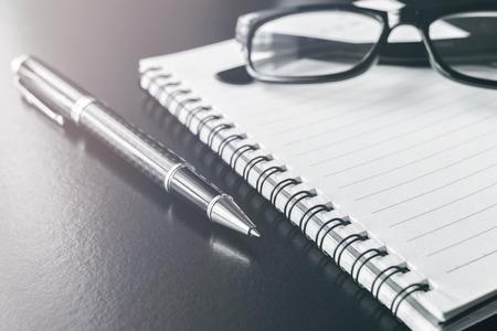papeles oficina: cuaderno y pluma en el escritorio de oficina, lugar de trabajo, el tono monocromático