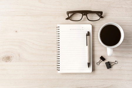 OFFICE DESK: Cup of coffee with notebook on wooden desk Stock Photo