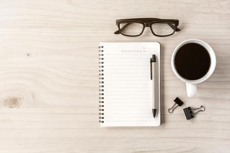 trompo de madera: Taza de café con el cuaderno en el escritorio de madera