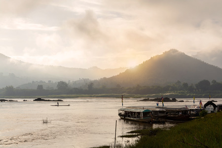 loei: Misty morning on the khong river with Silhouette of boat in loei province, Thailand