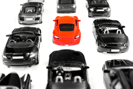 standing out from the crowd: Red toy car standing out from crowd of plenty identical black car on white background