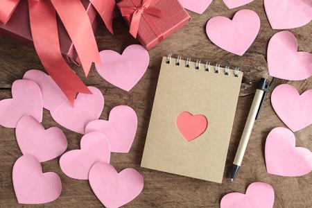 saint valentin coeur: forme de coeur rouge avec des fleurs et des notes sur la vieille table en bois, le concept Valentines Banque d'images