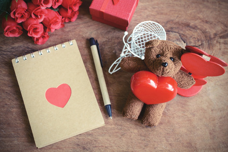 love abstract: Teddy bear with red heart shape and notebook on old wooden background, Valentines concept, Vintage tone Stock Photo