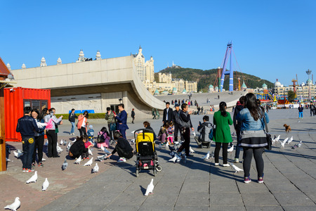 metre: Dalian, China - October 27, 2015 : People enjoy the activities in Xinghai Square. The Square covers total area of 1.1 million square metre.