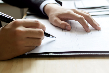 testimonial: Close up Human Hand Signing on Formal Paper at the workplace