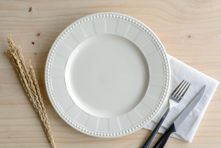 clean dishes: Empty dish with knife and fork on old wooden background, Top view Stock Photo