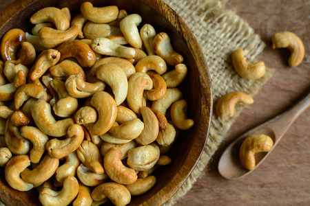 cashew nuts: cashew nuts with wooden spoon on sackcloth, Top view