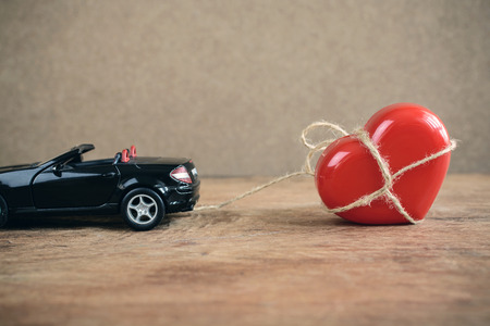 enslave: Heart which tied up with rope is towing by sports car, Love concept