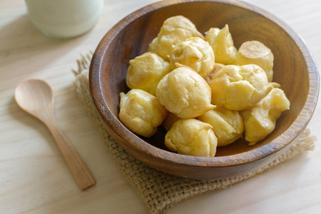 choux: Choux pastry cream puffs with milk on wooden table