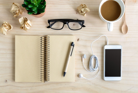 earphone: Blank notebook with earphone and a cup of coffee on wooden desk, Top view