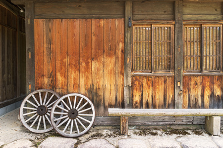wheel house: Old wooden house and Vintage wooden carriage wheel backdrop