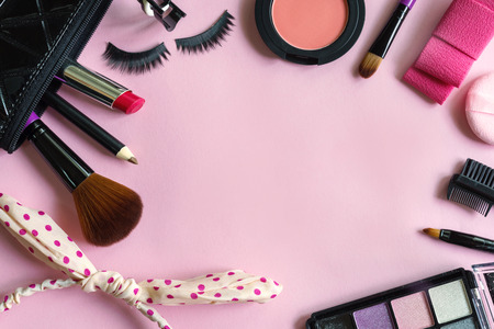various makeup products and cosmetics isolated on pink background