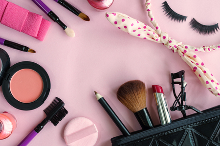 cosmetics products: various makeup products and cosmetics isolated on pink background