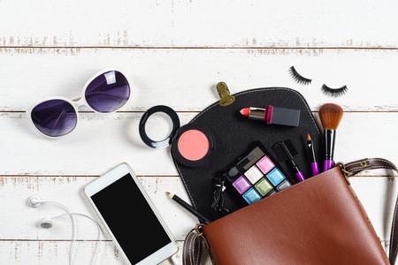 divers produits cosmétiques et de maquillage dans un sac à l'épaule sur fond blanc bois Banque d'images