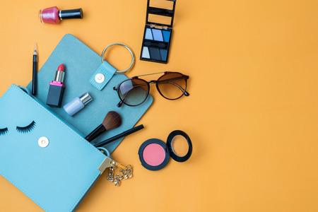 Moda kobiety essentials, kosmetyki, telefon, akcesoria makijaż na kolorowe tło, widok z góry