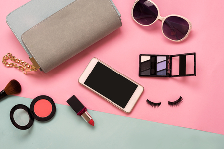 Mujer de la manera esenciales, cosméticos, teléfono móvil, accesorios de maquillaje aislados en el fondo colorido, Vista superior
