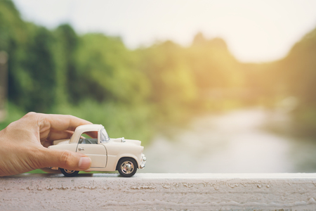 Hand holding a Car with landscape background, Travel concept, Vintage tone
